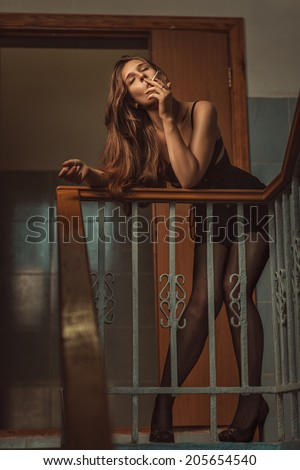 Woman of easy virtue smoke on the steps. - stock photo