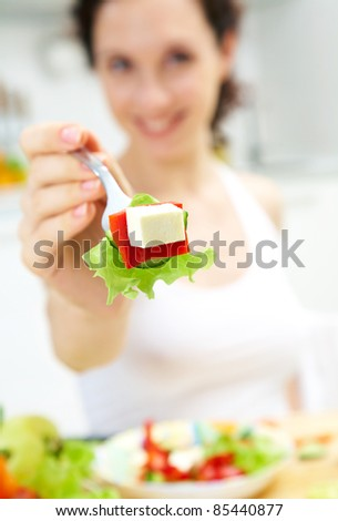 Woman offer fresh salad. Focus on food. - stock photo