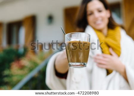 Woman offering cup of coffee outside home on autumn cold day.