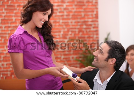 Woman offering man a small gift
