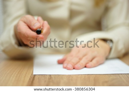 Woman offering pen to sign papers - stock photo