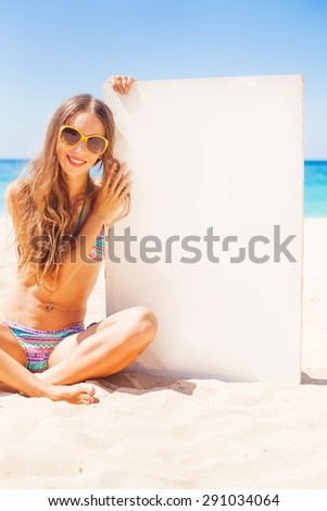woman on a beach holding a blank board for your text - stock photo