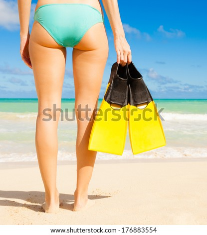 Woman on a beautiful beach in Hawaii about to go for a swim.  - stock photo