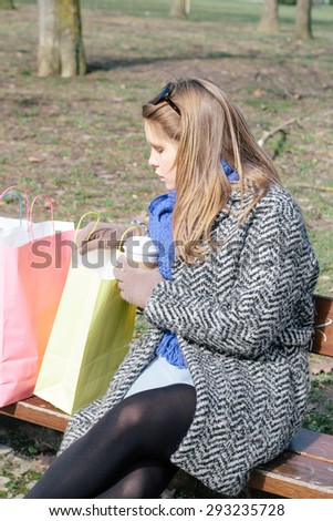 Woman on a bench holding a cup and shopping bags