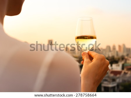 Woman on a city rooftop holding a glass of wine. - stock photo