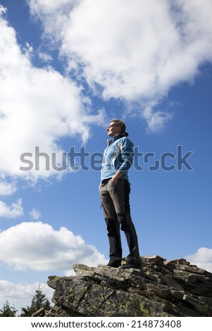Woman on a cliff enjoying nature after a trek