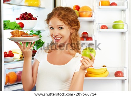 Woman on a diet to choose between healthy and unhealthy food near refrigerator - stock photo