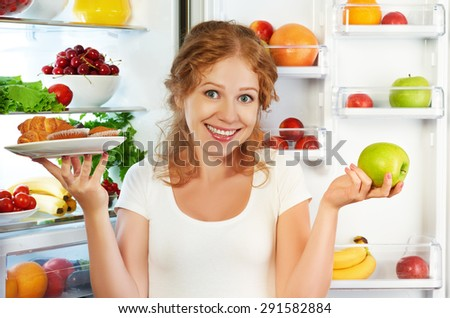 Woman on a diet to choose between healthy and unhealthy food near refrigerator