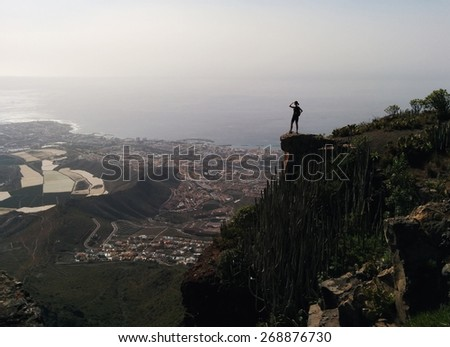 Woman on a edge of a mountain enjoying valley view. Tenerife, Canary Islands, Spain - stock photo