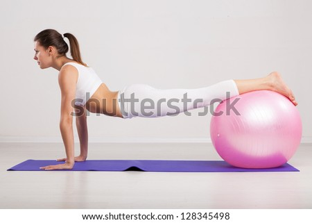 Woman on a fitness ball in a gym - stock photo