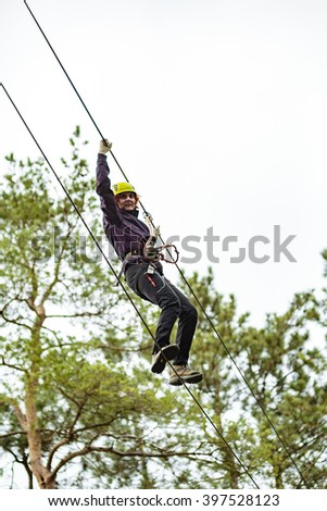 Woman on a high wire climbing in an adventure park