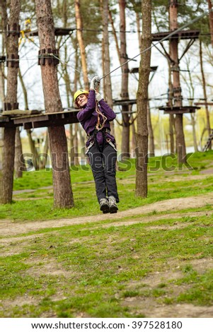 Woman on a high wire in an adventure park, having fun - stock photo