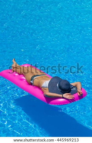woman on a lilo relaxing at the swimming pool