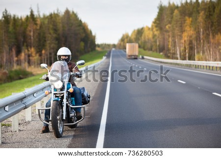 Woman on a motorcycle resting on the roadside of a country highway with empty road