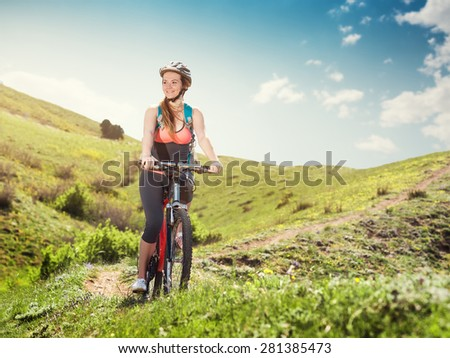 Woman on a mountain bike rides in the mountains of the beautiful nature. Portrait of a girl cyclist outdoors.
