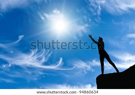 woman on a mountain top his arms in hand against the sunny sky - stock photo