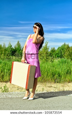 Woman on a road with a suitcase is waiting for a car. - stock photo