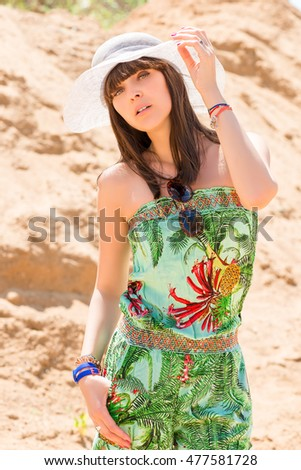 woman on a sandy beach in the hat summer warm day