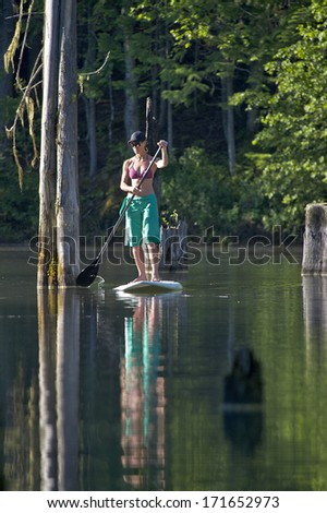 Woman on a stand up paddle boarding on calm water in a lagoon.