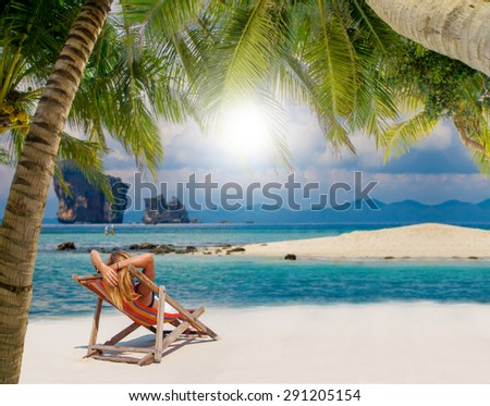 Woman on a tropical beach sunbathing - stock photo