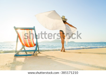 Woman on a tropical beach with hat - stock photo