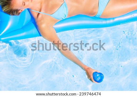 woman on an air mattress in the swimming pool - stock photo