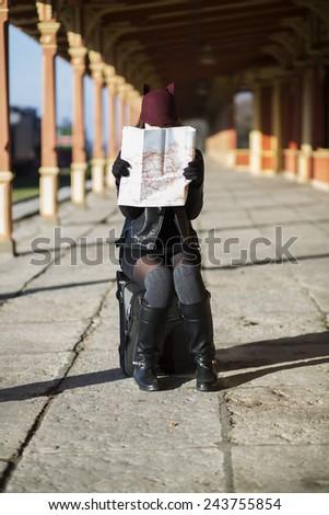 Woman on baggage examing map at empty platform - stock photo