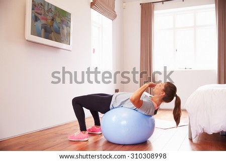 Woman On Ball Working Out To Fitness DVD On TV In Bedroom - stock photo