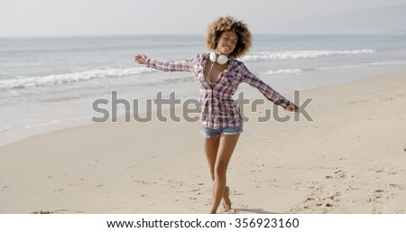 Woman on beach listening to music on smart phone happy dancing. - stock photo