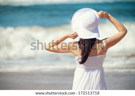 Woman on beach summer vacation looking the sea waves. Relaxing romantic girl enjoying summertime lifestyle.