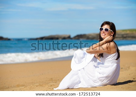 Woman on beach summer vacation sitting on the sand. Relaxed romantic girl enjoying summertime lifestyle looking the sea. Asturias, Spain. - stock photo