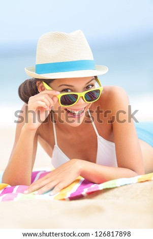 Woman on beach with sunglasses looking flirting at camera smiling happy and joyful during summer vacations holiday travel. Beautiful young multiethnic Asian Chinese / Caucasian hipster lying on beach. - stock photo