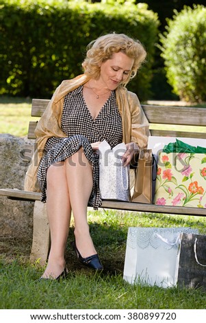 Woman on bench with bags of shopping