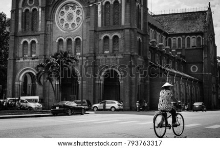Woman on bicycle in front of church
