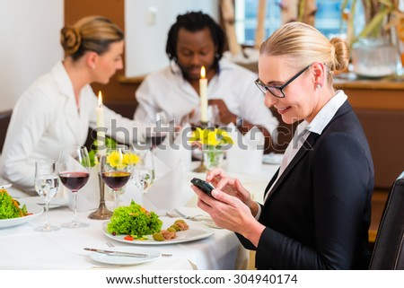 Woman on business lunch in restaurant checking mails on phone - stock photo