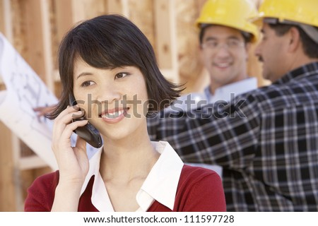 Woman on call with contractors working in background at construction site - stock photo