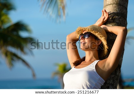 Woman on caribbean travel relaxing and resting under tropical palm trees. Happy brunette enjoying vacation and tranquility.