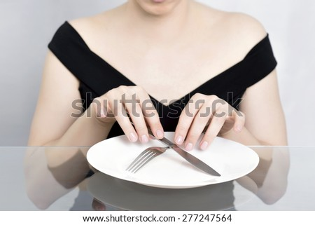 Woman on diet, dining in front of empty plate - stock photo