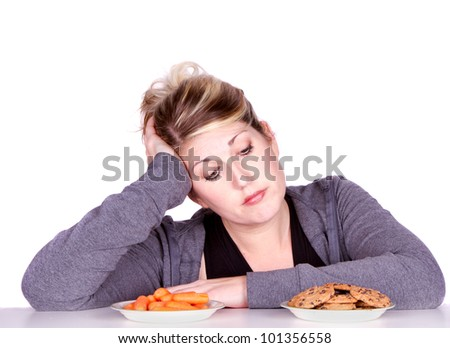 Woman on diet making eating choices, choosing between carrots or cookies.