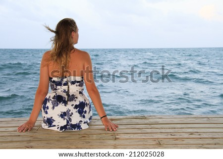 Woman on dock looking out toward ocean - stock photo