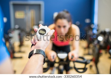Woman on exercise bike with trainer timing her at the gym - stock photo