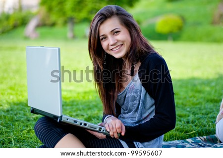 woman on grass with laptop in summer park