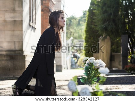 Woman on her knees in front of a grave