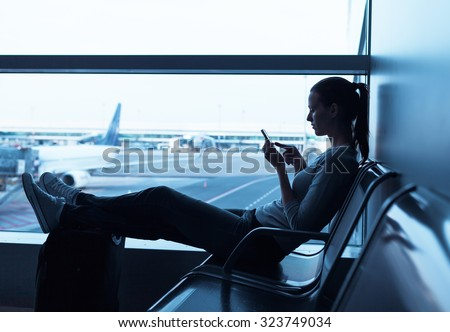 Woman on her smart phone waiting at the airport . - stock photo
