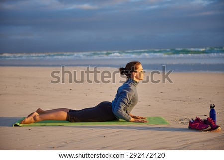 Woman on her yoga mat in the cobra pose on the beach at sunrise - stock photo