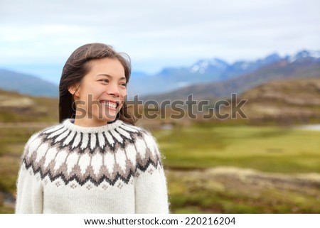 Woman on Iceland in Icelandic sweater. Portrait of girl happy smiling outdoors in nature wearing Icelandic sweater. Pretty Asian Caucasian multiracial female model - stock photo