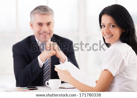 Woman on job interview. Cheerful young woman looking over shoulder and smiling while mature man in formalwear sitting on background