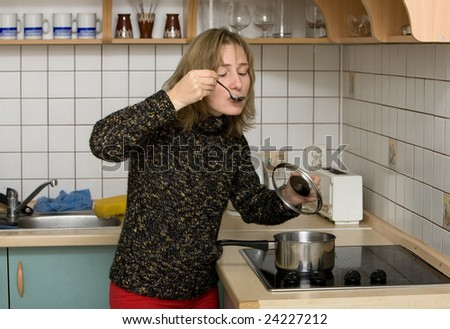 woman on kitchen tasting dinner from a spoon