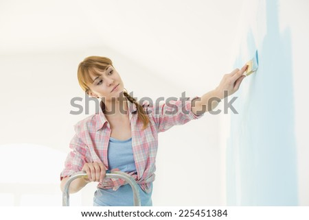 Woman on ladder painting wall with paintbrush - stock photo