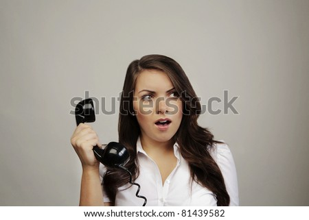 woman on old BT telephone looking surprised - stock photo